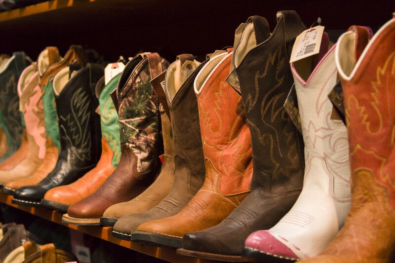 This photo shows a row of cowboy boots in varying shades of brown white, and black on a shelf in a shoe store, representing the best boots affiliate programs.