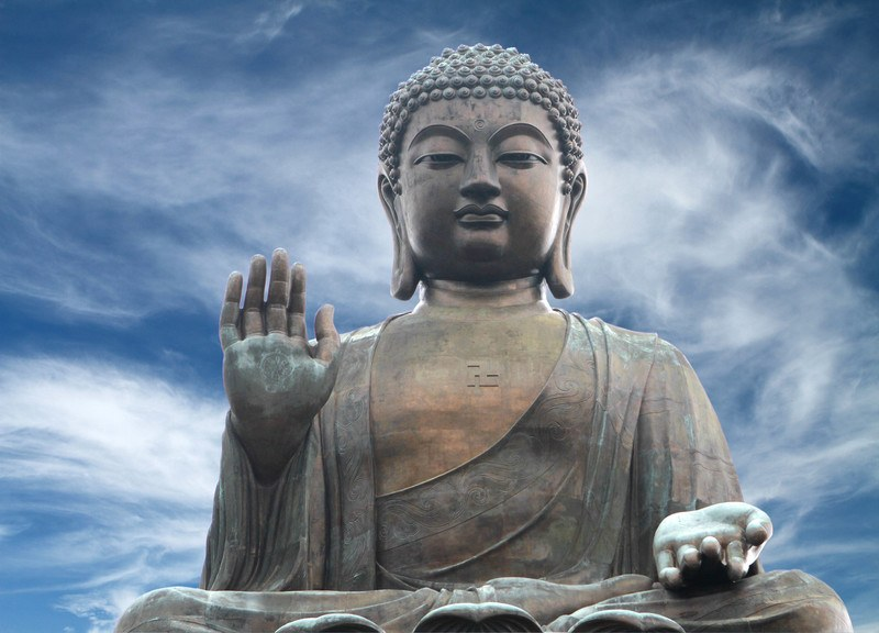This photo of the Tian Tan Buddha statue in Hong Kong has a bronzed look and sits before a dramatic blue sky with white feathery clouds, representing the best Buddhism Affiliate Programs.
