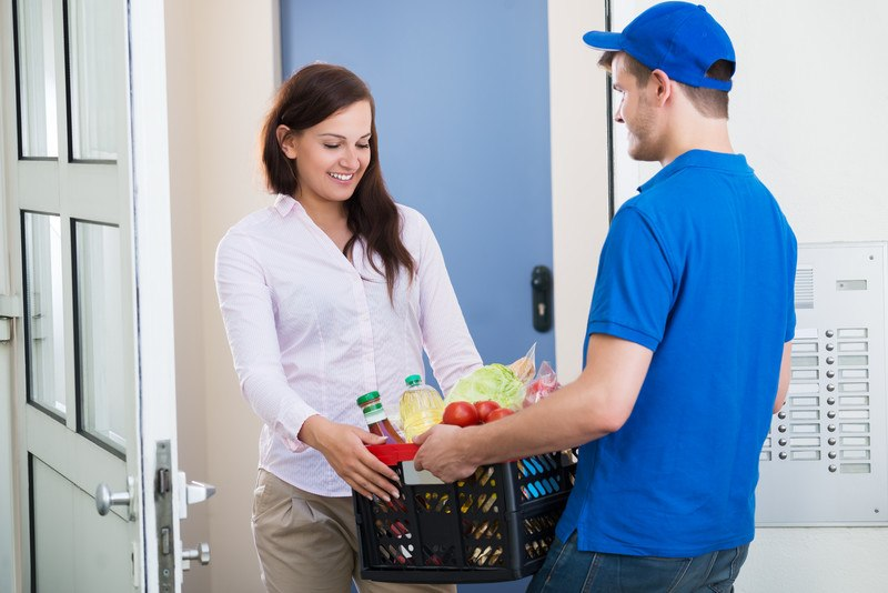 This photo shows a smiling dark-haired woman in a pink shirt standing in a doorway, accepting a crate of food from a smiling delivery man in blue clothing, representing the best food delivery affiliate programs.