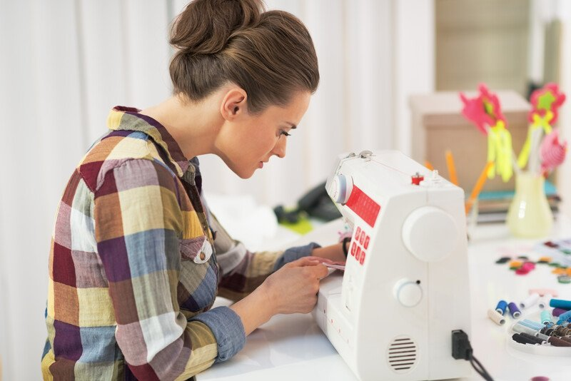 This photo shows a brunette woman in a bun and a plaid shirt using a sewing machine in what appears to be a craft room, representing the best handmade craft affiliate programs.