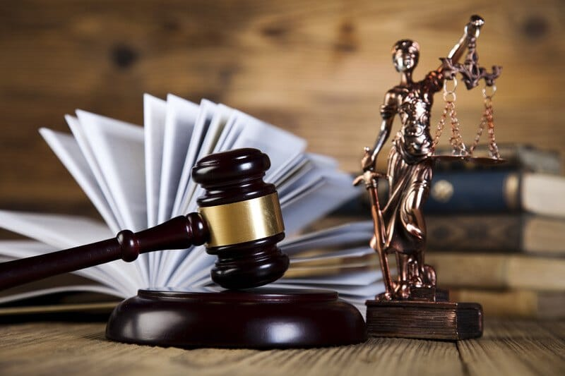 This photo shows a gavel, an open book, and a bronze figurine of a woman holding a sword and a set of scales, representing the best legal affiliate programs.