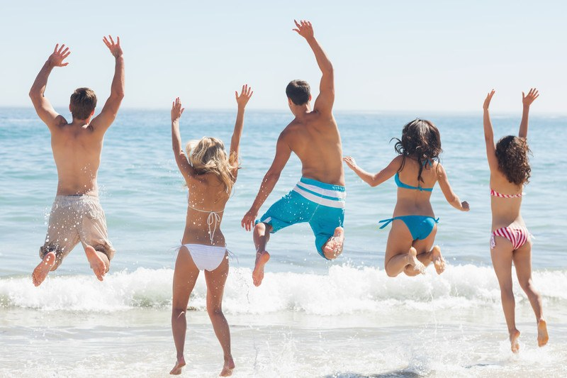 This photo shows a back view photo of a group of friends in varying colors of swimsuits playing in the water at a beach, representing the best swimwear affiliate programs.