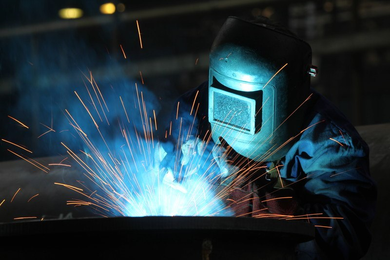 This photo shows a man in a welding helmet welding something while orange sparks fly out in several different directions, representing the best welding affiliate programs.