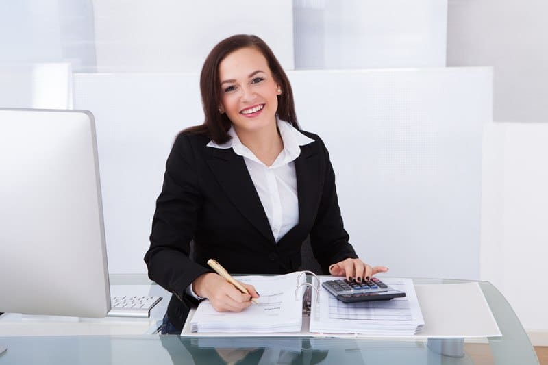 This photo shows a smiling dark haired woman in a white shirt and black jacket sitting in a white room with a transparent table, an open laptop, a stack of accounting papers, and a calculator, representing the question, do accountants make good money?