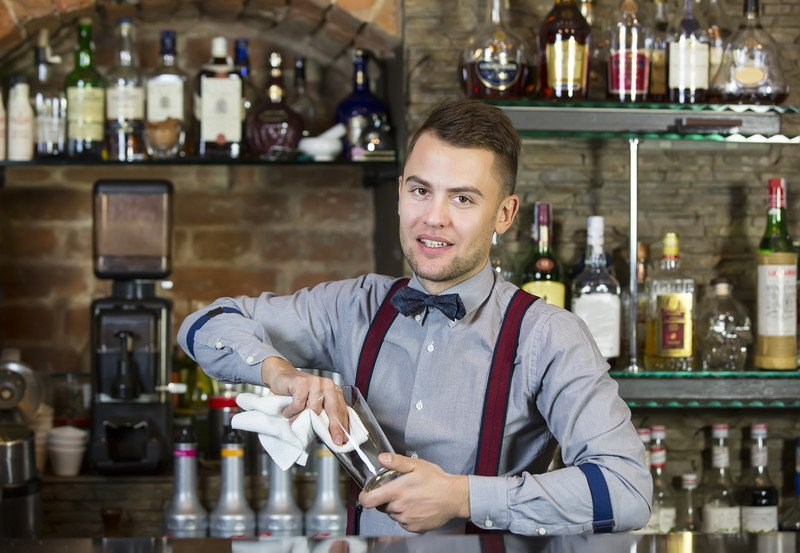This photo shows a handsome young bartender in a gray shirt, red suspenders, and blue bowtie wiping a glass behind a bar, representing the question, do bartenders make good money?
