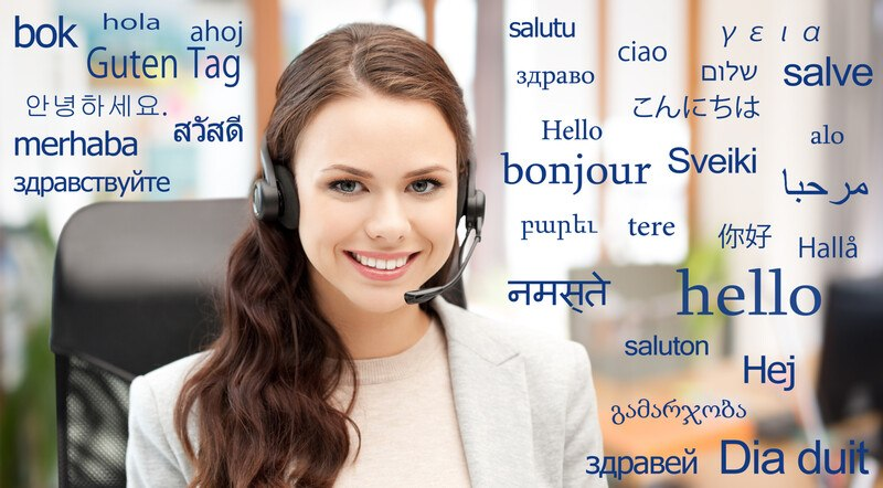 This photo shows a smiling brunette woman with a headset and light-colored clothing sitting in an office chair surrounded by words in blue text meaning 'hello' in several languages, representing the question, do translators make good money?
