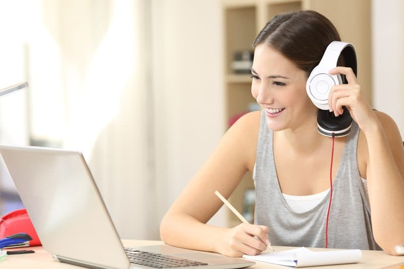 woman in casual clothes working at home with her laptop and headset