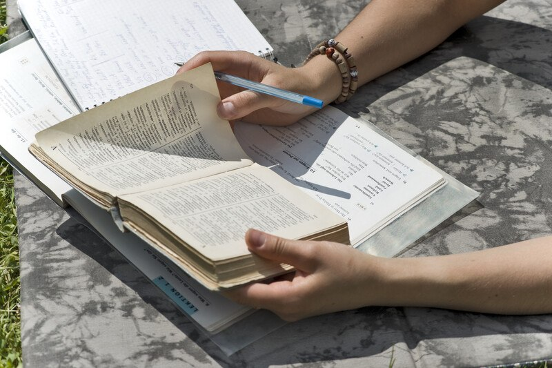 This photo shows a woman's hands holding a pen and an open dictionary over a binder, as if she is studying different words to use when translating text from one language to another.