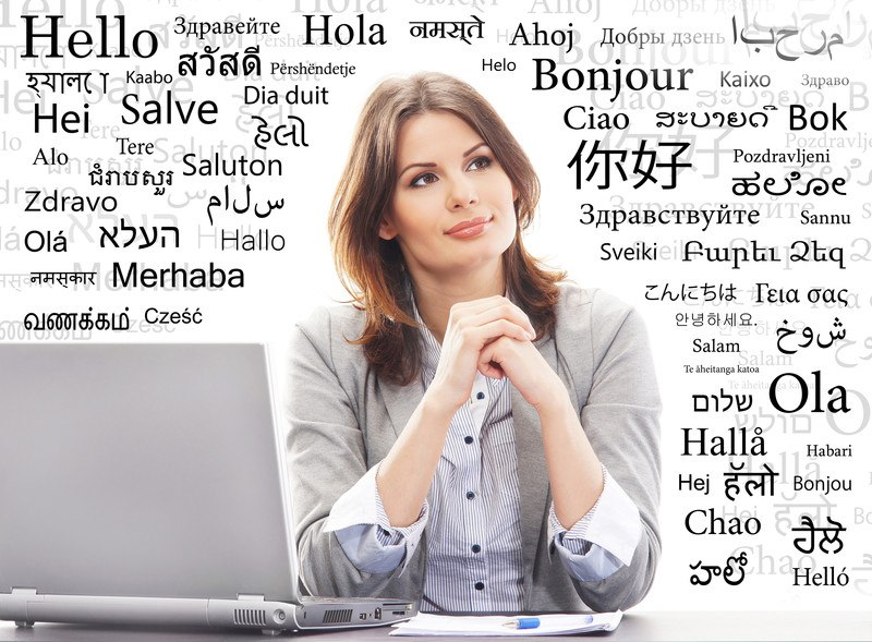 This photo shows a brunette woman in a gray sweater and blue and white striped shirt leaning forward on her elbows on a table next to a laptop and a paper with a pen, surrounded by words in black text in several languages.