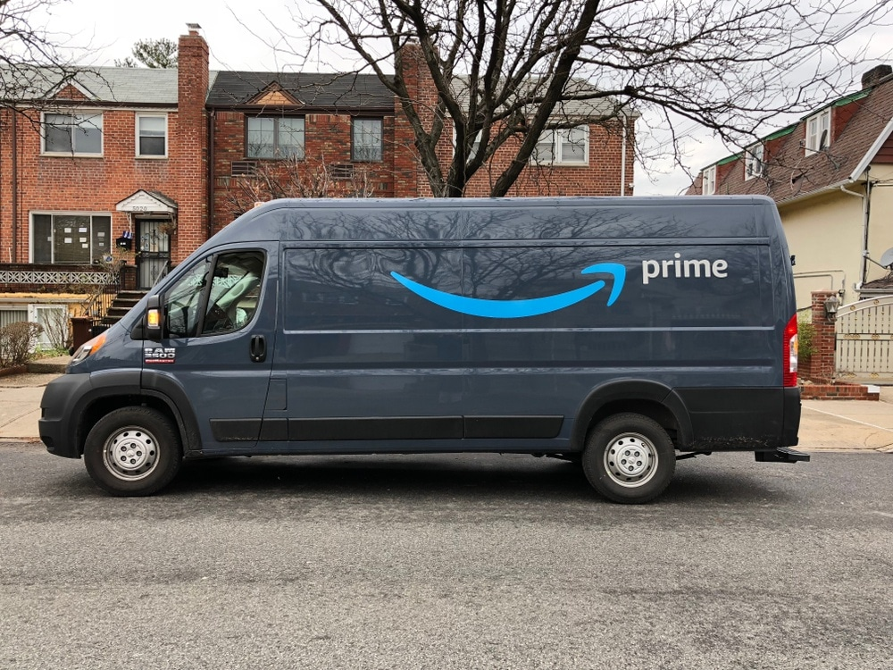 amazon prime delivery van in front of brick houses