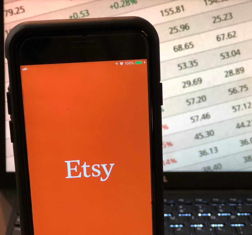 close photo of etsy app on smartphone with sale prices on laptop in background