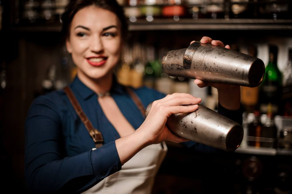female bartender with red lipstick and two shakers