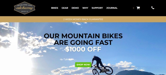 This screenshot of the home page for Alchemy Bicycles has a black and gold header and navigation bar with white and gold text above a photo showing a cyclist on a mountain bike against a blue sky with white clouds, behind black and white text with a green call to action button.