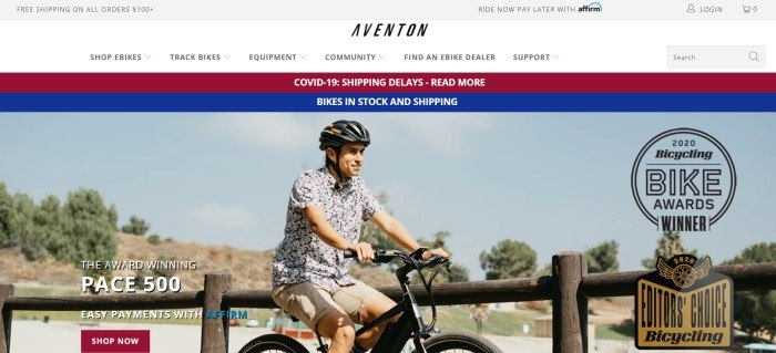 This screenshot of the home page for Aventon has a gray header, a white navigation bar, and a red and blue announcement bar above a photo of a smiling man in a black helmet, a black and white print shirt, and khaki shorts riding a black bike in what appears to be a park, along with white text and a red call to action button.