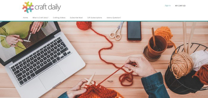 This screenshot of the home page for Craft Daily has a white header with a multicolored logo above an overhead photo showing a laptop with a knitting demonstration on the screen, two balls of orange yarn, a pair of scissors, a mobile phone, and an orange coffee cup resting on a wooden table, as well as a pair of hands holding knitting needles.