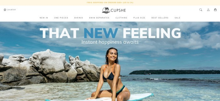 This screenshot of the home page for Cupshe has a beige header, a white navigation bar, and a large photo of a smiling dark haired woman in a back bikini sitting on a surf board in the ocean, behind white and blue text.