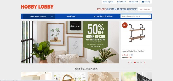 This screenshot of the home page for Hobby Lobby has a gray background, a red logo in the upper left corner, a blue navigation and search bar with white text, a photo showing green plants and photos of green plants on a wall, along with a green text section with white text announcing a sale, and a photo on the right side of the page of a set of hanging shelves.