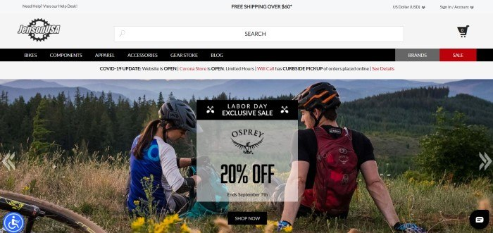 This screenshot of the home page for Jenson USA has a gray header and search bar, a black navigation bar with white text, a white announcement bar, and a large photo showing the rear view of a young man and young women in bicycle clothing and helmets sitting in a meadow near their bikes, opening their backpacks as they look over an evergreen forest with mountains in the background, along with a gray and black sales announcement and a black call to action button.