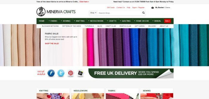 This screenshot of the home page for Minerva Crafts has a gray header, a white search bar, a dark green navigation bar, and a photo showing rows of fabric in varying solid colors ranging from white to teal, above a bar showing social media icons and a dark green announcement for free delivery, and a row of small photos with text depicting categories of items this store carries.