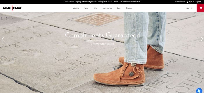 This screenshot of the home page for Minnetonka has a black header, a white navigation bar, and a photo showing a man's legs in jeans and brown suede Minnetonka boots standing on concrete that had been written in, along with white text and call to action button.