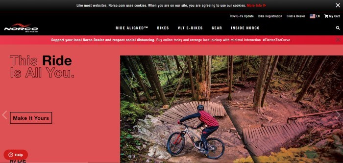 This screenshot of the home page for Norco has a black header and navigation bar with white and red text, a red announcement bar, and a red background in the main section with black text on the left side of the page and a photo of a cyclist in a red and black shirt and helmet cycling down a stone and wooden ramp in the mountains on the right side of the page.