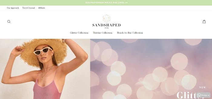 This screenshot of the home page for Sandshaped has a green header, a white navigation bar, and a set of side by side photos, with a woman in sunglasses, a straw hat, and a pink one-piece swimsuit on the left side of the page and a photo of what appears to be blurry lights in pink and purple on the right side of the page.