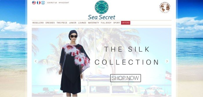 This screenshot of the home page for Sea Secret has an ocean scene for a background behind a white main section with an aqua-colored logo, a white navigation bar, and a photo of a mannequin in a black coverup with a pink floral print, as well as black text announcing a fashion collection.