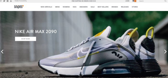 This screenshot of the home page for Snipes has a gray header, a white navigation bar with black text, and a photo of a silver, yellow, white, and black sneaker lying on a sidewalk near a white fence, along with white text and a white call to action button on the left side of the page.