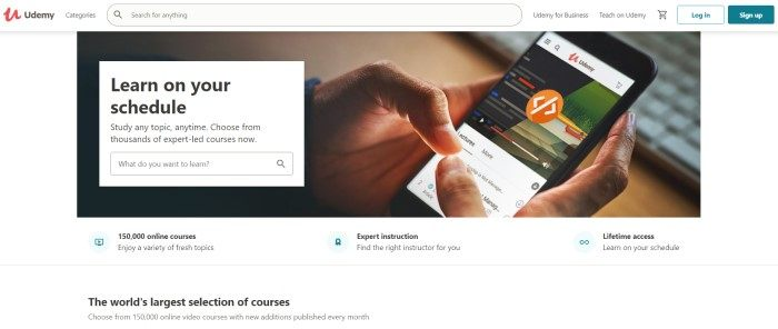 This screenshot of the home page for Udemy has a white search bar and background and a large photo of a man's hands using the Udemy app on a mobile device, as well as a white search section with black text, and black text below the photo describing different features of this platform.