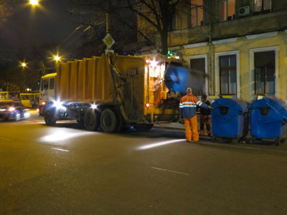 trash collectors picking up dumpsters at night