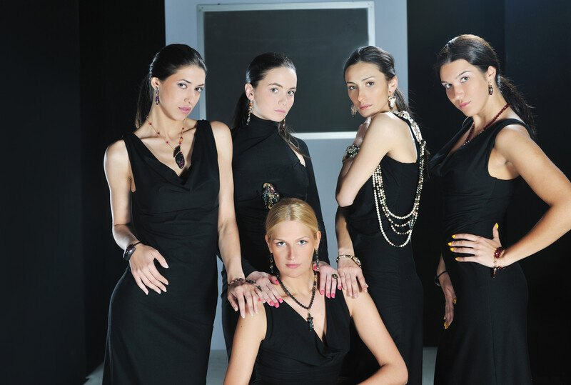 This photo shoes five women in black fashion dresses and nice jewelry posing in front of a black and gray background, representing the best luxury fashion affiliate programs.