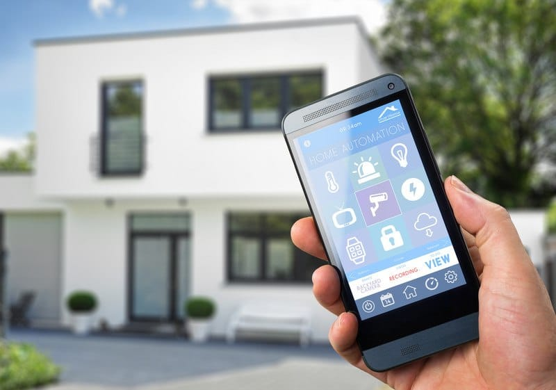 This photo shows a white home in the background with a man's hand holding a mobile device with home connection icons on the screen in the foreground, representing the best smart home affiliate programs.