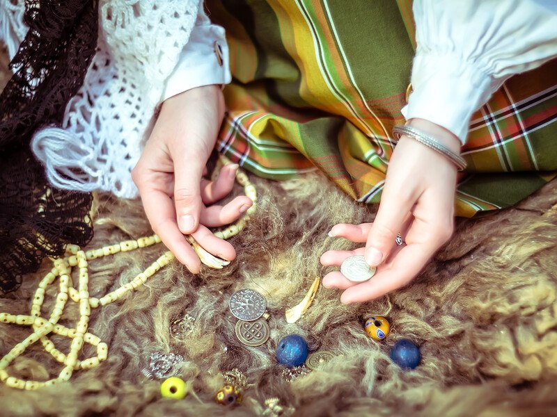 This photo shows the hands of a young woman sorting through various beads, coins, and runes as if preparing to cast a spell, representing the best witchcraft affiliate programs.