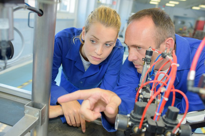 This photo shows a woman and a man in blue jumpsuits looking at a piece of equipment in a lab, representing the question, do mechanical engineers make good money?