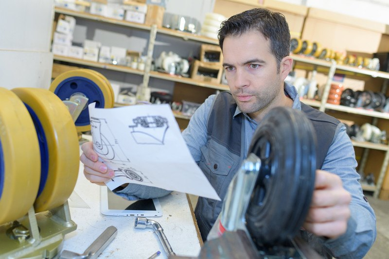 This photo shows a dark-haired male mechanical engineer in a blue shirt and gray vest comparing a design sketched on a piece of paper to a black piece of equipment in a manufacturing shop.
