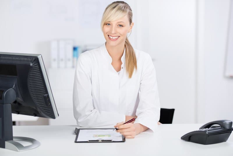 This photo shows a smiling blonde woman in a white shirt holding a pen near a desk with a phone, a monitor, and a clipboard with medical information on it.