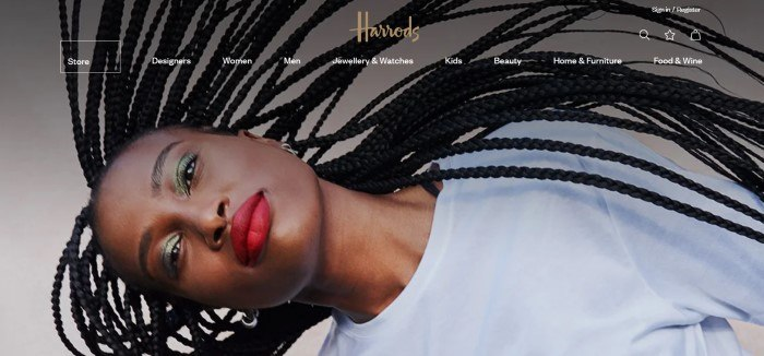 This screenshot of the home page of Harrods has a transparent navigation bar with white text overlaying a sideways photo of a dark-skinned woman with black braids, bright red lipstick, and a white shirt.