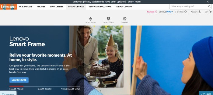 This screenshot of the home page for Lenovo has a black header, a white navigation bar with black text and an orange logo, above a gray secondary navigation bar, and a large photo of a woman in a blue hat putting a frame around a picture of a young girl and a woman cutting a birthday cake, along with white text and a blue call to action button.