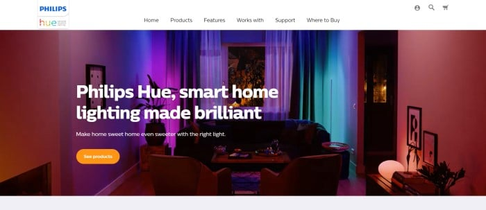 This screenshot of the home page for Philips-Hue has a white navigation bar with black text above a large photo of an indoor living room with lighting set to red, blue, green, and purple, along with white text and an orange call to action button.
