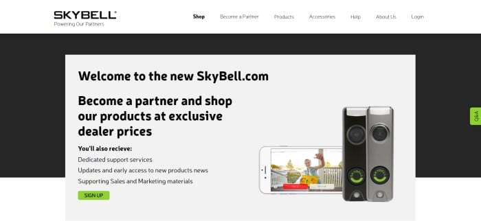 This screenshot of the home page for SkyBell has a white navigation bar with black text above a black and white main section with black text and a green call to action button on a white background section on the left side of the page and a photo of a mobile device with someone waving from the front porch next to two doorbell cameras.