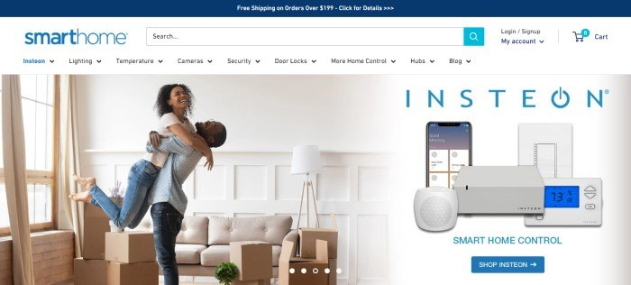 This screenshot of the home page for Smarthome has a blue announcement bar above a white search bar and navigation bar, along with a large photo of a smiling man and woman hugging in a white living room with a large window, a beige couch, and several boxes, next to a photo showing Smarthome equipment.