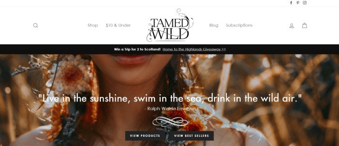 This screenshot of the home page for Tamed Wild shows a black header and a closeup of the chin and shoulders of a woman with long flower-twined hair, behind white text and two black call to action buttons.