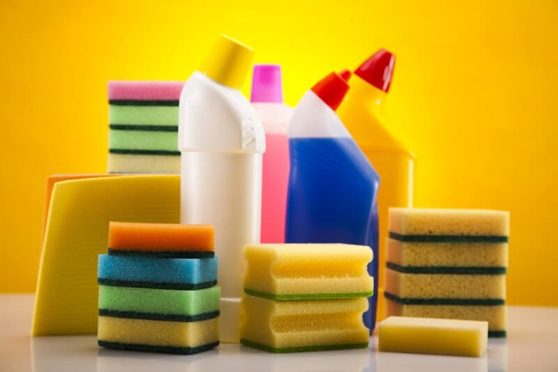 This photo shows several multicolored cleaning bottles and sponges on a glossy white surface in front of a bright yellow background, representing the best cleaning products affiliate programs.