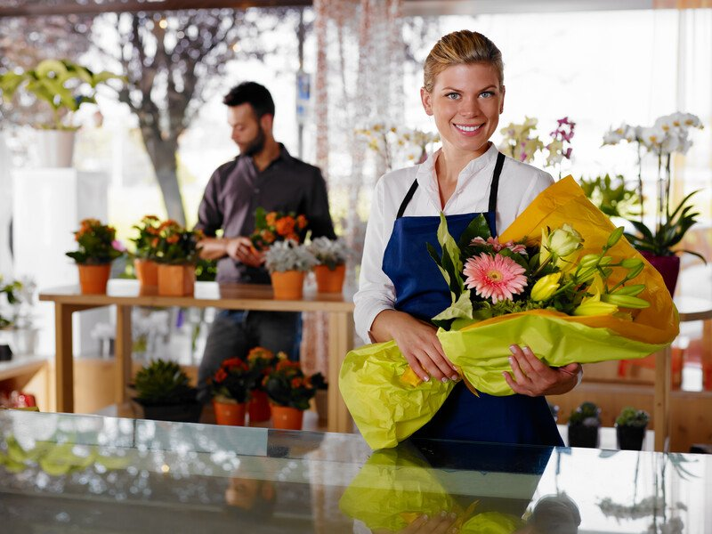 This photo shows a smiling blonde woman in a white shirt and blue apron, holding a pink and yellow bouquet in yellow paper, in what appears to be a florist shop with a man browsing through floral arrangements in the background, representing the best flowers affiliate programs.