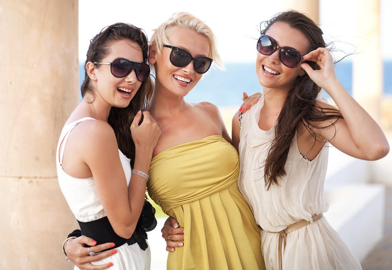 This photo shows two smiling brunette women and a smiling blonde woman in dresses and sunglasses on a balcony, representing the best sunglasses affiliate programs.