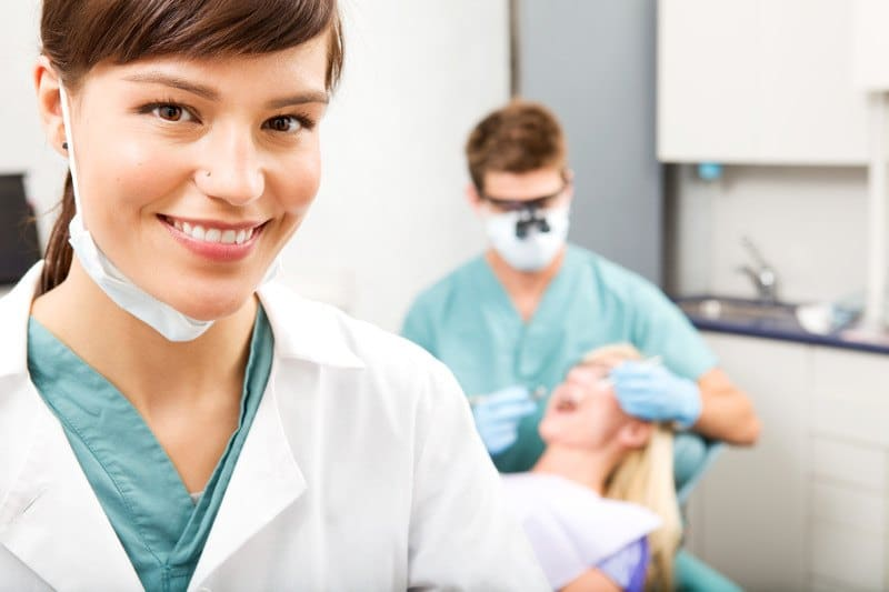 This photo shows a smiling brunette woman in aqua scrubs and a white lab coat standing in a dentist office in front of a blonde woman lying in a dental chair with her mouth open, receiving an oral exam from a dentist in aqua scrubs, representing the question, do dental hygienists make good money?