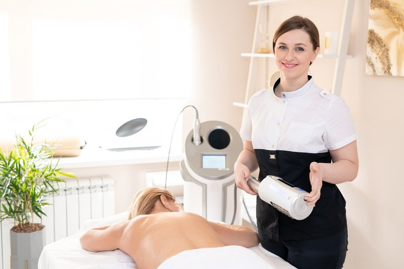 This photo shows a smiling brunette massage therapist in white and black clothing, holding a massage roller while a blonde woman in a white towel lies on a table in front of her in a bright room.