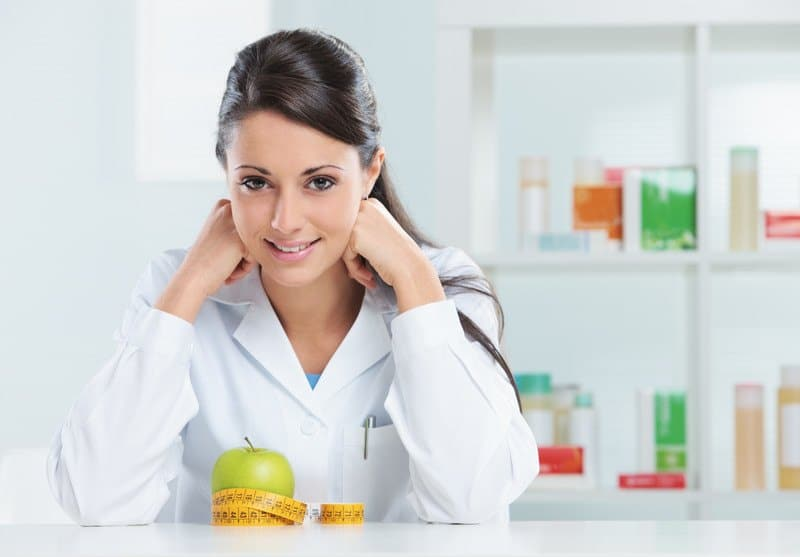 This photo shows a smiling brunette woman in a white lab coat sitting in a white office with what appears to be nutritional supplements on shelves behind her and an apple with a tape measure on a white table in front of her, representing the question, do nutritionists make good money?