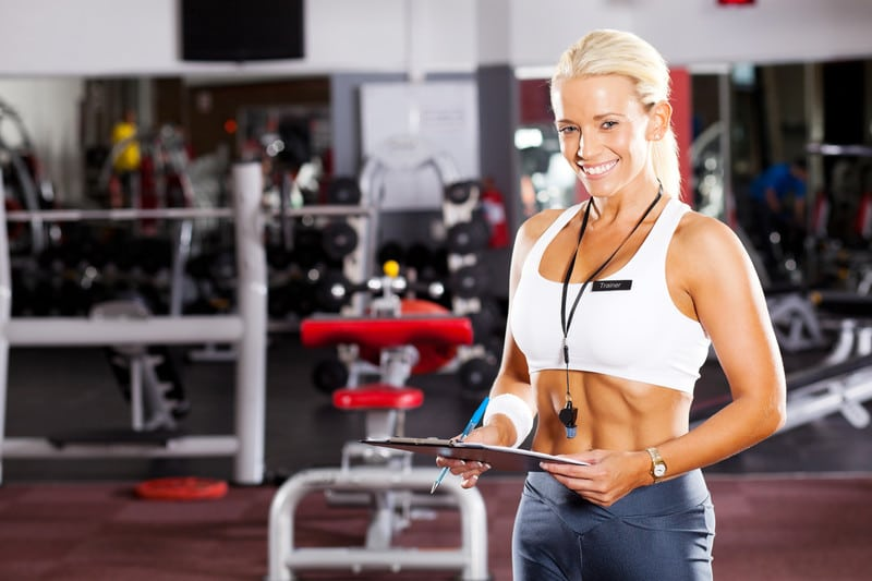 This photo shows a smiling blonde female personal trainer in white and black clothing standing in a gym, representing the question, do personal trainers make good money?