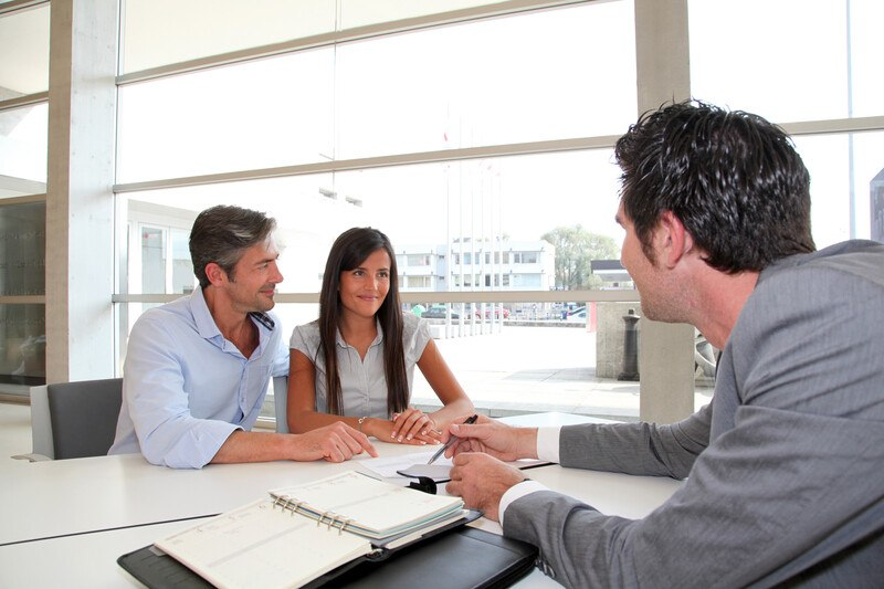 This photo shows a smiling couple sitting at a desk in a financial institution while a dark-haired man in a gray suit shows them some paperwork.